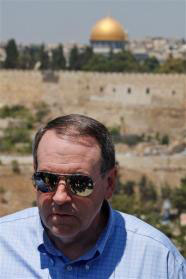 Back-dropped by the golden shrine of the Dome of the Rock in Jerusalem's Old City, former Arkansas governor and US presidential hopeful Mike Huckabee is seen during his tour in the east Jerusalem neighborhood of Ras al Amud, Monday, Aug. 17, 2009.